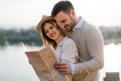 Touristische junge Paare unter Verwendung der Karte als Führer stockbild