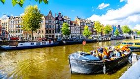 Touristische Kanal-Boote, die bei Anne Frank House am Prinsengracht Prinzen Canal in der Jordaan-Nachbarschaft in Amsterdam festm stockfoto