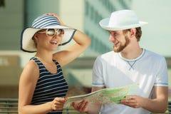 Touristische Paare in der Stadt, die oben Richtungen auf Karte schaut Stockfotografie