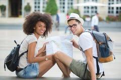 Touristische Paare, die beim dem Sitzen in der Stadt und Lächeln gehen stockbilder