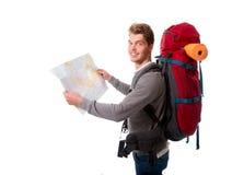 Touristische schauende Karte des jungen attraktiven Wanderers, die großes Rucksack lugagge trägt Lizenzfreies Stockbild