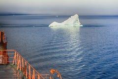 Touristische Schiffssegel nah an kleinem Eisberg Stockbild