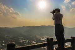 Touristische Stellung auf einem oberen Zaungeländer, das ein Foto der Reisterrassen bei Bada Yuanyang macht lizenzfreie stockfotografie