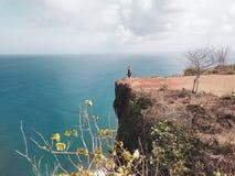 Touristische Stellung des Mädchens auf der Klippe stockfotos