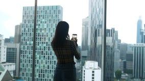 Touristische Stellung des Mädchens am Fenster benutzt den Smartphone, der Foto auf einer Handyansicht einer Wolkenkratzerhöhe in  stock footage
