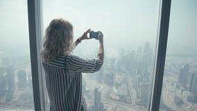 Touristische Stellung des Mädchens am Fenster und an einem Handy fotografiert stock video footage