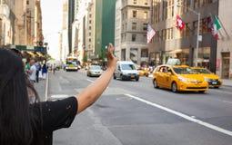 Touristischer Anruf ein gelbes Fahrerhaus in Manhattan mit typischer Geste Lizenzfreie Stockbilder