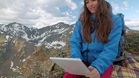 Touristischer Frauenfreiberufler benutzt einen Computer in der Natur und sitzt auf dem Gras nahe bei einer Gasfackel Berge werden stock video