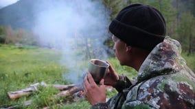 Touristischer Getränktee von einem Becher nahe dem Feuer stock video