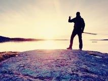 Touristischer Kerl, der Fotos der erstaunlichen Seelandschaft auf Handydigitalkamera macht Lizenzfreie Stockfotos