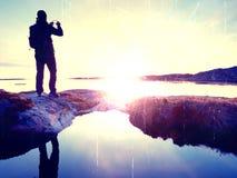 Touristischer Kerl, der Fotos der erstaunlichen Seelandschaft auf Handydigitalkamera macht Wandereraufenthalt auf einem Felsen na Lizenzfreies Stockbild