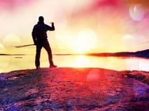 Touristischer Kerl, der Fotos der erstaunlichen Seelandschaft auf Handydigitalkamera macht Wandereraufenthalt auf einem Felsen na Stockfotos