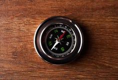 Touristischer Kompass, der auf einem Holztisch liegt Stockbild