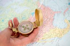 Touristischer Kompass in der Hand über Karte Lizenzfreie Stockbilder