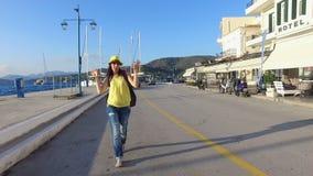 Touristischer Mädchen Brunette in einem gelben T-Shirt, Blue Jeans, ein gelber Hut und mit einem farbigen Rucksack geht entlang
