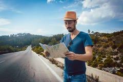 Touristischer Mann, der die Karte verloren ist auf einer Reise liest Stockfotografie