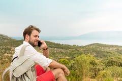 Touristischer Mann, der an einem Handy unter Hügeln spricht Lizenzfreie Stockfotografie