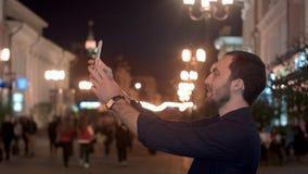 Touristischer Mann, der herein Foto mit Smartphone an der Nachtstadt macht Stockbild