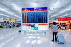 Touristischer Mann, der mit seinem Gepäck steht und den Flug auf dem Abfahrtszeitbrett überprüft Stockfotos