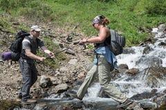 Touristischer Mann hilft einem Mädchentouristen zur Kreuzung des Gebirgsflusses Lizenzfreie Stockfotos