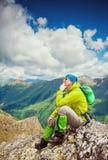 Touristischer Mannwanderer auf die Oberseite des Berges Stockfoto