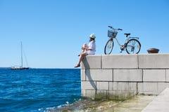 Touristischer Radfahrer der jungen Frau mit Stadtfahrrad in der Stadt nahe dem Meer Stockfoto