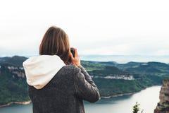 Touristischer Reisender des Fotografen, der auf die grüne Oberseite auf dem Berg hält Handin der digitalen Fotokamera, Wandereran lizenzfreie stockfotografie