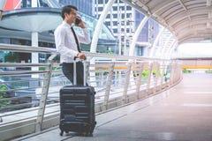 Touristischer Reisender des Geschäfts mit Gepäck unter Verwendung seines Handys lizenzfreie stockfotografie