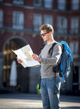 Touristischer schauender Stadtplan des jungen Studentenwanderers in Feiertage reisen Lizenzfreie Stockfotos