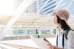 Touristischer Wanderer des glücklichen Asiatinreisenden mit dem modischen Blick, der Richtung auf Standortkarte beim Reisen im Au Lizenzfreie Stockfotos
