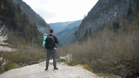 Touristischer Wanderer des Mannes mit Rucksack szenische Ansichtgebirgsflusslandschaft genie?end Reisewanderer, der weg schaut Re stock video footage