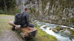 Touristischer Wanderer des Mannes mit Rucksack szenische Ansichtgebirgsflusslandschaft genie?end Reisewanderer, der weg schaut Re stock footage