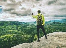 Touristischer wandernder Gebirgspfad des Mannes, macht Foto telefonisch lizenzfreie stockfotografie