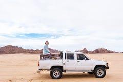 Touristisches amerikanisches Mädchen in der Wadirumwüste Jordanien mit Auto lizenzfreie stockfotos