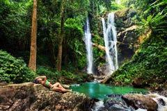 Touristisches aufgeregtes Hawaii-Frau durch Wasserfall Stockfoto