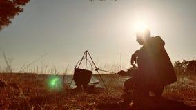 Touristisches Bier des Mannes sitzen Lebensstil durch Feuerpartei in Schattenbild-Sonnenlichtsonnenuntergang der Natur kampierend stock video footage
