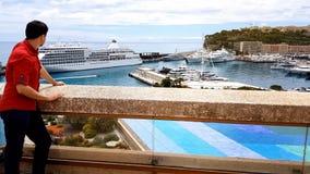Touristisches Bleiben auf Terrasse des Luxushotels und Beobachten des Seehafens mit Yachten stockfotografie