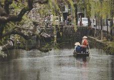 Touristisches Boot auf dem Kanal an alter Stadt Kurashiki in Okayama, Japan Kurashiki ist eine historische Stadt, die in West gel lizenzfreies stockbild