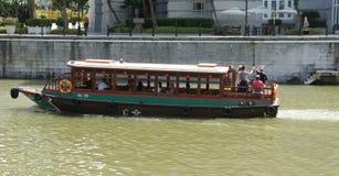 Touristisches Boot, das Singapur vom Flussufer erforscht Lizenzfreie Stockbilder