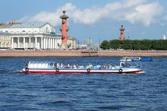 Touristisches Boot ` Neman-` mit asiatischen Touristen auf dem Hintergrund des Spuckens von Vasilyevsky-Insel Stockfotos