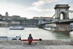 Touristisches girst, das auf der roten Niederlassung sitzt und Ansicht zum B sieht Lizenzfreie Stockfotos