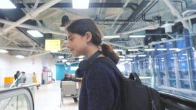 Touristisches junges Mädchen jugendlich mit Rucksack mit Koffer oben hinunter die Rolltreppe der Flughafenwartelebensstil für das stock footage