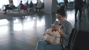 Touristisches Mädchen benutzt Smartphone im Flughafenaufenthaltsraum stock video footage