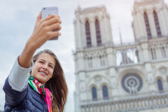 Touristisches Mädchen des Jugendlichen nimmt selfie mit Kathedrale von Notre Dame de Paris frankreich Lizenzfreies Stockfoto