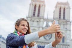 Touristisches Mädchen des Jugendlichen nimmt selfie mit Kathedrale von Notre Dame de Paris frankreich Lizenzfreie Stockbilder