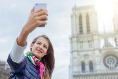Touristisches Mädchen des Jugendlichen nimmt selfie mit Kathedrale von Notre Dame de Paris frankreich Stockfoto