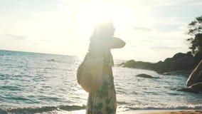 Touristisches Mädchen durch den Ozean mit einem Rucksack stock video
