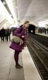 Touristisches Mädchen mit dem lustigen Beutel, der das tra wartet Lizenzfreie Stockfotos