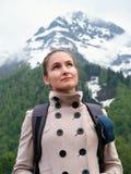 Touristisches Mädchen mit einem Rucksack auf dem Hintergrund von Schnee-mit einer Kappe bedeckten Bergen lizenzfreie stockfotografie