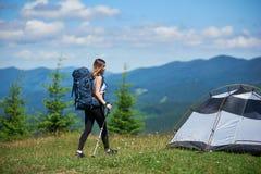 Touristisches nahes in den Bergen mit Rucksack- und Trekkingsstöcken morgens kampieren der Frau lizenzfreie stockfotografie